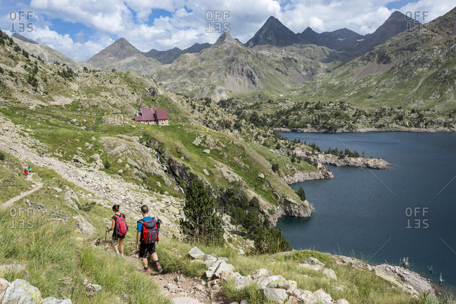 July 30, 2017: Hikers make their way along the the long distance footpath called the GR11 towards Refugio Respomuso in the Spanish Pyrenees, Huesca, Spain, Europe