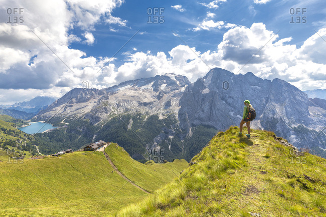 Hiker looks towards Viel del Pan Refuge with Marmolada in the background, Pordoi Pass, Fassa Valley, Trentino, Dolomites, Italy, Europe