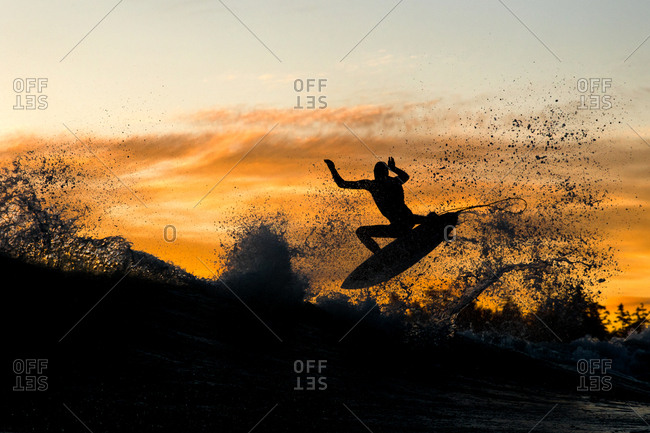 Silhouette of surfer mid-air above a wave