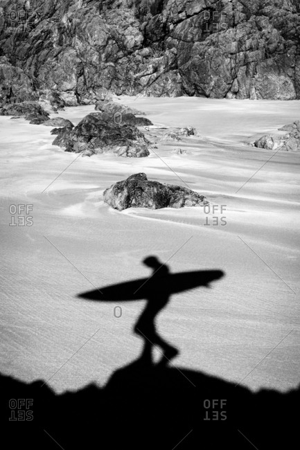 Shadow of surfer on a beach in black and white
