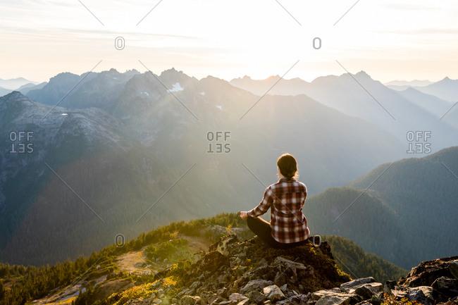 Woman meditating on mountainside at sunrise