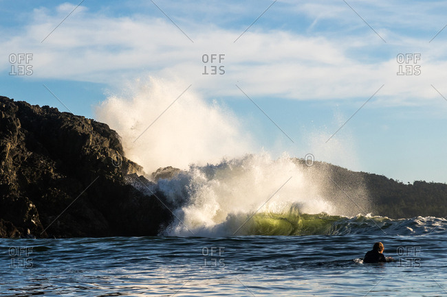 Surfer in the water by crashing waves