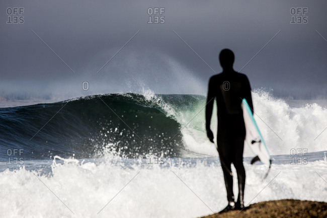 Surfer standing by water watching crashing waves