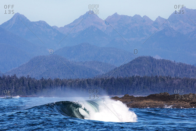 Cresting blue waves in the ocean with mountains in the background