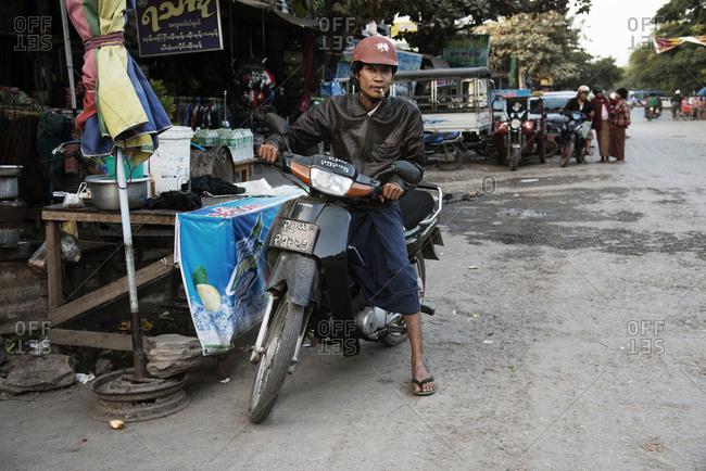 Mandalay, Myanmar - December 22, 2015: Man on a motorcycle smoking a cigarette stopped at a roadside stand