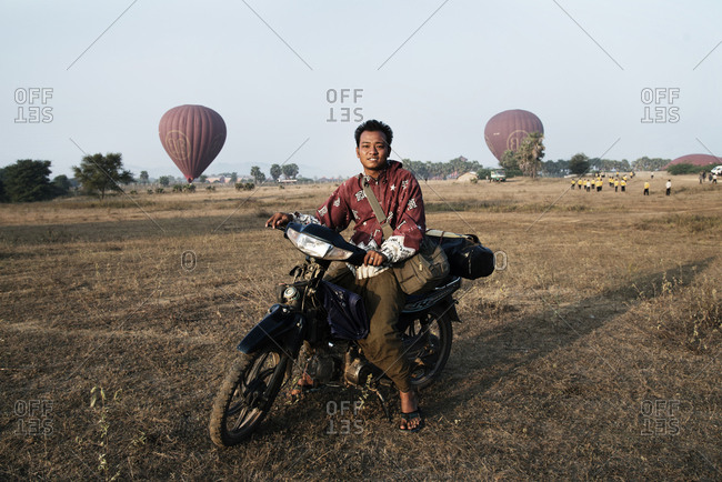 Bagan, Myanmar - December 25, 2015: Young man on motorcycle in a field with hot air balloons rising in the distance