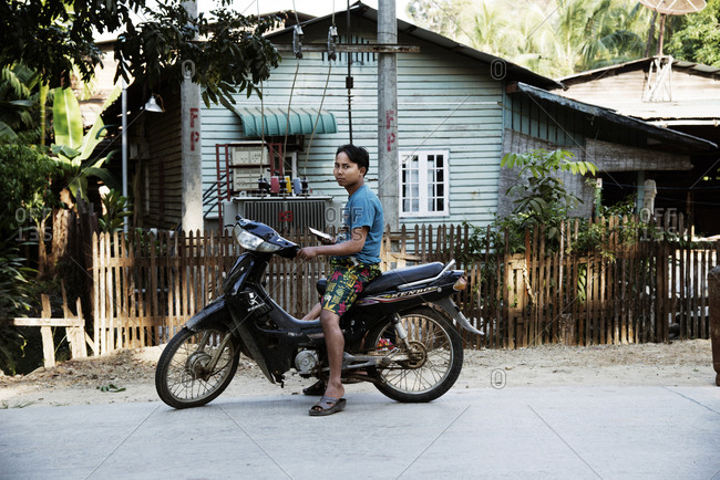 Ngapali, Myanmar - December 31, 2015: Young man on a motorcycle holding a phone parked along a street in front of a house