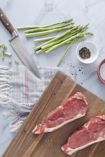 Raw steaks are prepped on a cutting board for grilling