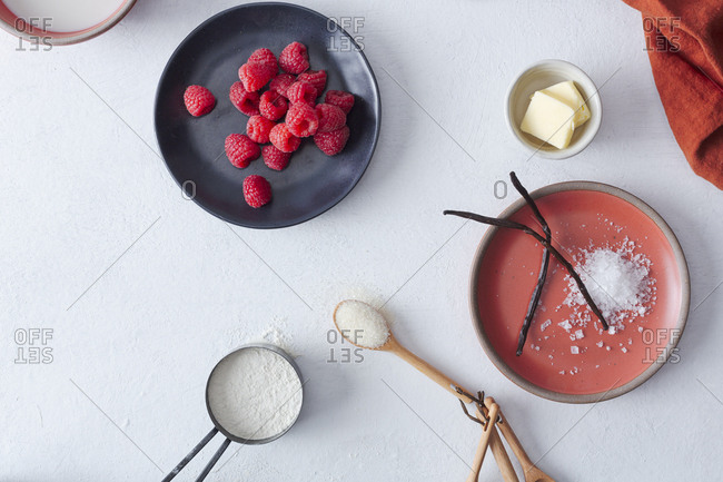 Baking ingredients including butter, sugar, vanilla bean and raspberries spread out on counter