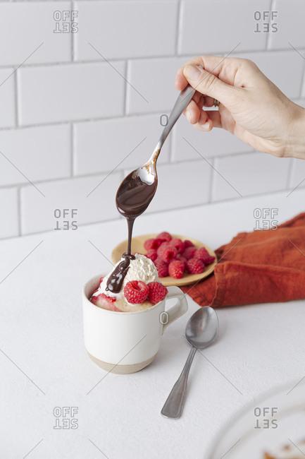 Hand drizzles chocolate onto mug cake