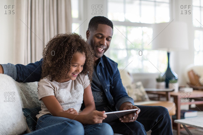 African American father and daughter using digital tablet together
