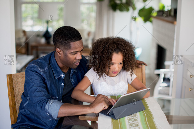 African American father helping daughter with homework using digital tablet