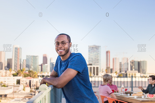 Portrait of young adult male at a rooftop party with city skyline