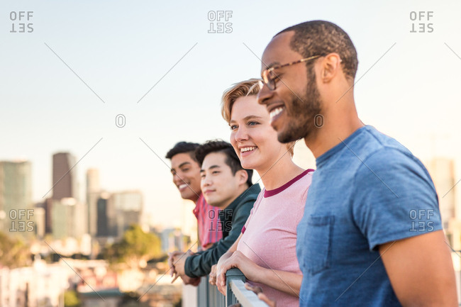 Group of friends looking out at city skyline view on a rooftop