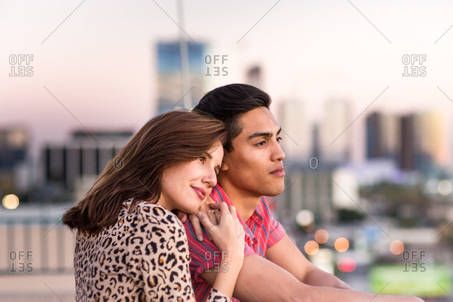Young adult couple looking out across city skyline