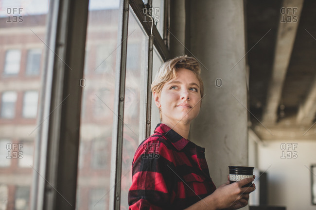 Young female looking out of window in loft apartment thinking