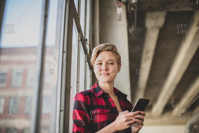Portrait young female in loft apartment holding smartphone