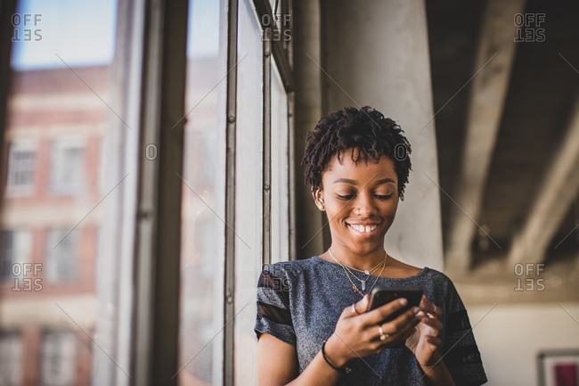Young african american female in loft apartment looking at smartphone