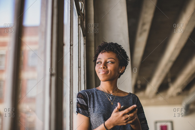 Young african american female looking out of window in loft apartment holding smartphone