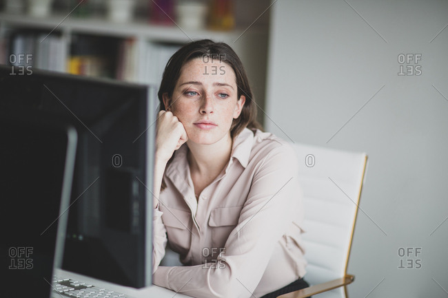 Female business executive in an office looking out of window thinking