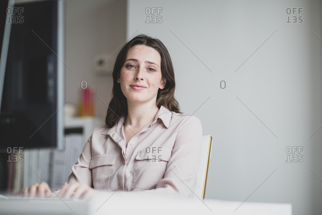 Portrait of a female business executive working in an office on a desktop computer