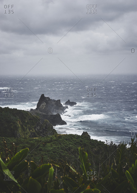 Rough seas smashing against rocks off the coast of Green Island on a cloudy day