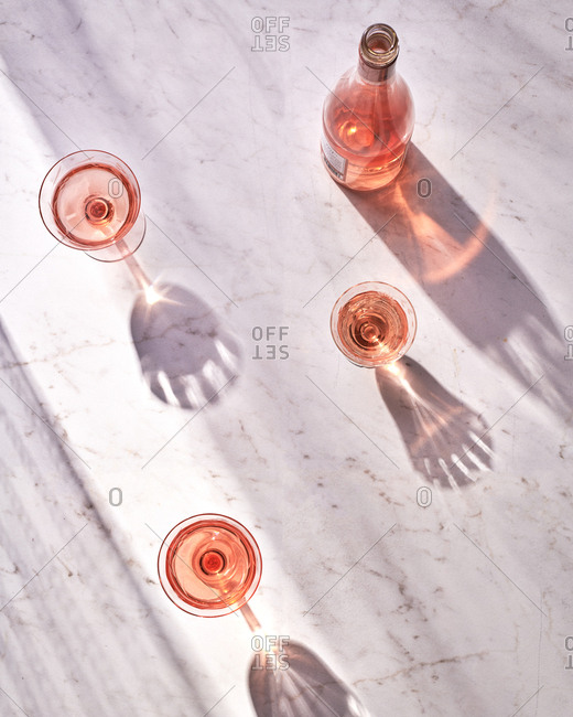 A bottle of Rose served in three vintage glasses on a marble surface in the afternoon light