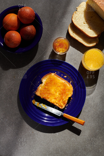 Orange Marmalade on toast on a blue plate with a butter knife on the plate beside blood oranges and orange juice