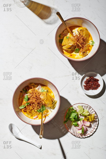 Khao Soi Kai with mustard greens on a white marble backdrop