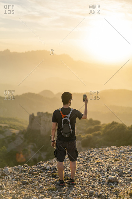 Spain- Barcelona- Natural Park of Sant Llorenc- man hiking and taking a picture of the view at sunset