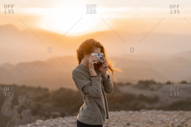 Spain- Barcelona- Natural Park of Sant Llorenc- woman taking a picture with vintage camera at sunset