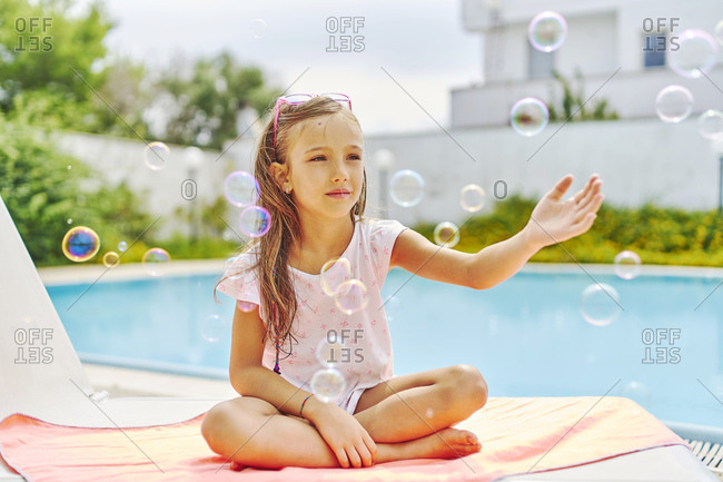 Girl playing with soap bubbles at the poolside