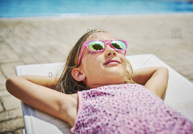 Girl with sunglasses lying at the poolside
