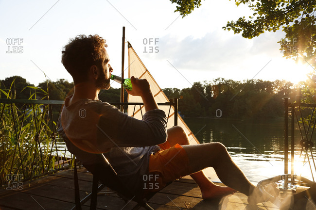 Young man with drinking a beer on a jetty next to sailing boat