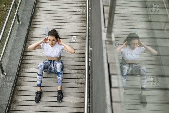 Young woman doing situps on a footbridge