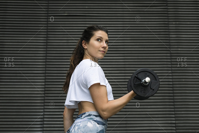 Young woman doing weight workout outdoors