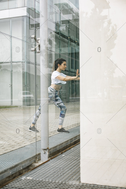 Young woman doing stretching exercise at glass facade
