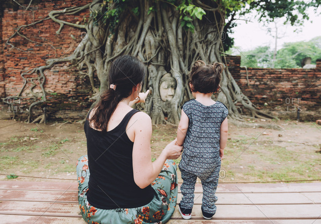 Thailand- Ayutthaya- Mother and daughter visiting the Buddha head in between tree roots at Wat Mahathat