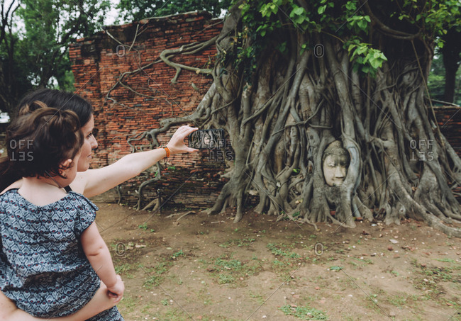 Thailand- Ayutthaya- Mother and daughter taking a photo of the Buddha head in between tree roots at Wat Mahathat
