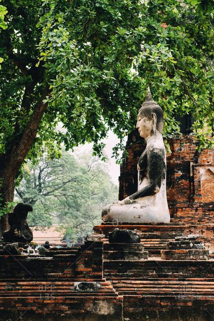 Thailand- Ayutthaya- Buddha statue surrounded by brick pagodes at Wat Mahathat