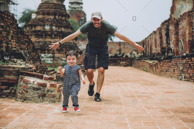 Thailand- Ayutthaya- Father and daughter running in the ancient ruins of a temple at Wat Mahathat
