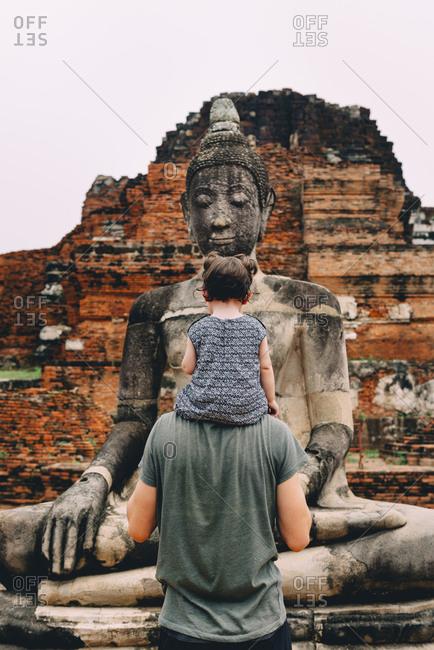 Thailand- Ayutthaya- Father and daughter looking at a Buddha statue at Wat Mahathat