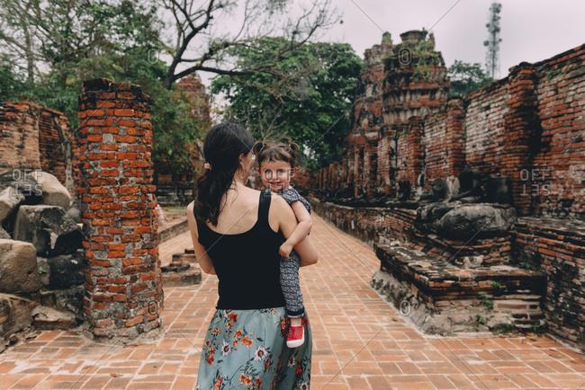 Thailand- Ayutthaya- Mother and daughter walking through the ancient ruins of a temple at Wat Mahathat
