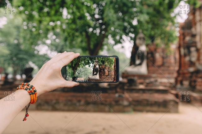 Thailand- Ayutthaya- Woman taking a photo of a Buddha statue at Wat Mahathat