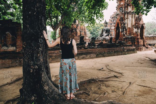 Thailand- Ayutthaya- Woman looking at a Buddha statue at Wat Mahathat