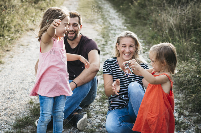 Happy family with two daughters playing with confetti on a field path