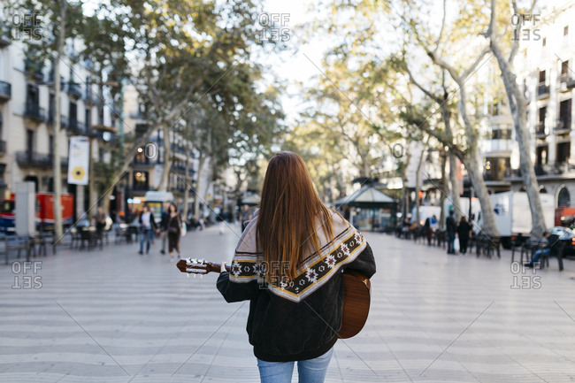 Red-haired woman playing the guitar in the city- rear view