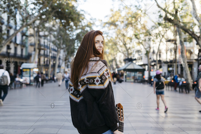 Red-haired woman with a guitar in the city