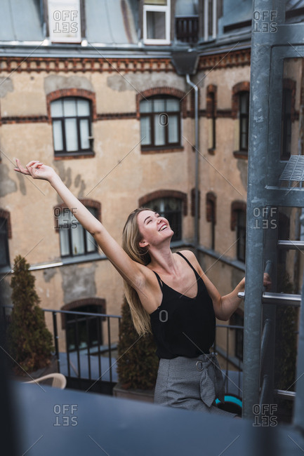 Happy young woman on balcony clambering a fire escape