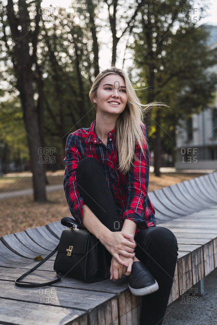 Portrait of fashionable young woman with hand bag sitting on bench outdoors